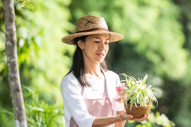Bewässerungsbaum der hübschen jungen frau im garten am sonnigen sommertag. frau, die draußen in der sommernatur im garten arbeitet. landwirtschaft, gartenarbeit, landwirtschaft und menschenkonzept.