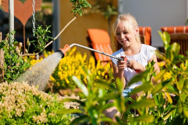 Bewässerungsblumen des glücklichen mädchens im hinterhof