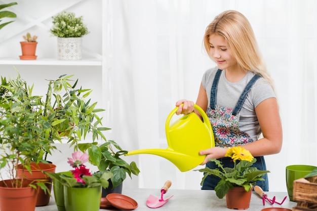 Bewässerungsblumen des jungen mädchens des hohen winkels