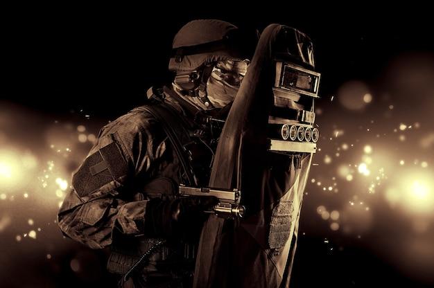 Bewaffnet mit einer pistole bedeckt sich ein soldat in einer kugelsicheren weste mit einem schild. gemischte medien