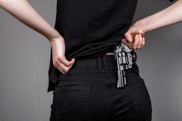 Bewaffnetes mädchen in schwarzen jeans versteckt ihre pistolenpistole hinter ihrem rücken. versteckte bedrohung killerfrau.