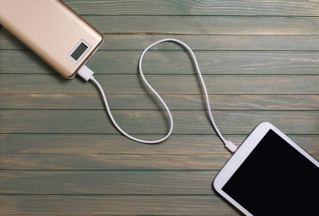 Bewegliche energiebank und tablet-pc auf hölzernem hintergrund