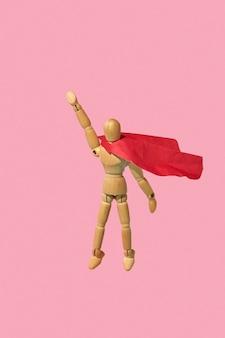 Bewegliche miniatur-artikulationsschaufensterpuppe in einem roten umhang fliegt mit erhobener hand als superheld oder übermensch hoch