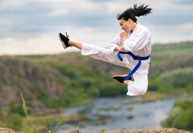 Bewegliche sportliche junge frau, die kickboxen übt und mit ausgestrecktem bein und geballten händen in die luft springt