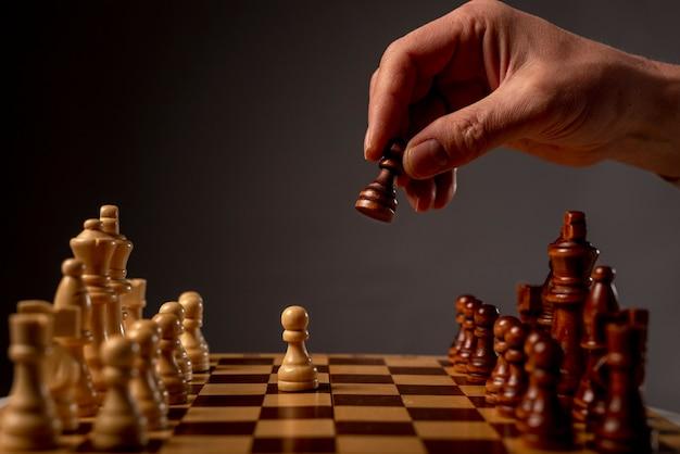 Beweglicher bauer der männlichen hand auf schachbrett, startspiel. geschäftsentscheidungskonzept.