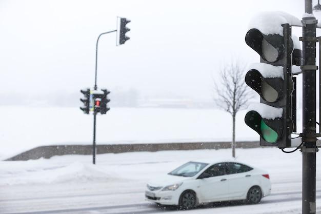 Bewegliches auto auf der stadtstraße des dammes während eines starken schneefalls, grüne ampel auf vordergrund