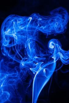 Bewegung blauer rauch auf schwarzem hintergrund.