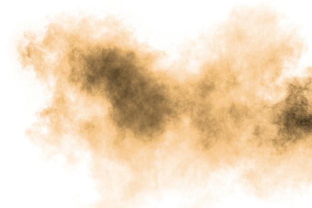 Bewegung der braunen staubexplosion einfrieren. bewegung des braunen pulvers stoppen. explosives braunes pulver auf weißem hintergrund.