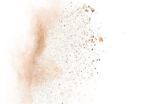 Bewegung des explodierenden braunen pulvers einfrieren. abstraktes design der braunen staubwolke gegen weißen hintergrund.