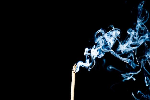 Bewegung des rauches vom räucherstäbchen auf schwarzem hintergrund