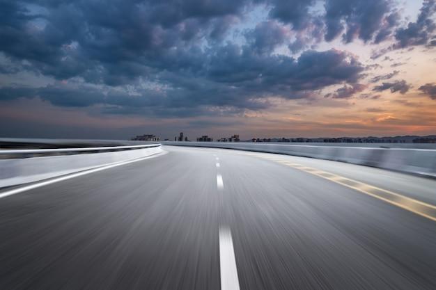 Bewegung-unscharfe landstraße in den dämmerungswolken
