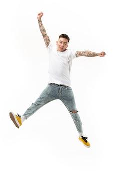 Bewegungsfreiheit. luftaufnahme des hübschen glücklichen jungen mannes, der gegen weißen studiohintergrund springt und gestikuliert. laufender kerl in bewegung oder bewegung.