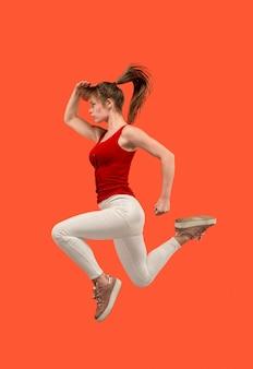 Bewegungsfreiheit. mid-air-aufnahme einer hübschen glücklichen jungen frau, die gegen den orangefarbenen studiohintergrund springt und gestikuliert. laufendes mädchen in bewegung oder bewegung.