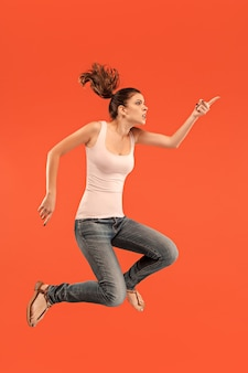 Bewegungsfreiheit. mid-air-aufnahme einer hübschen glücklichen jungen frau, die gegen ein orangefarbenes studio springt und gestikuliert.