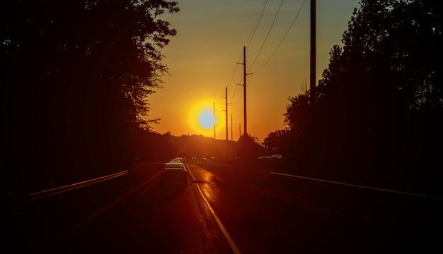 Bewegungsunschärfe autobahn verkehr im sonnenuntergang straße läuft durch den wald.