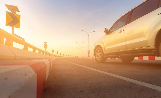 Bewegungsunschärfe des autos, das auf kurvenstraße mit verkehrszeichen und direktem sonnenlicht fährt