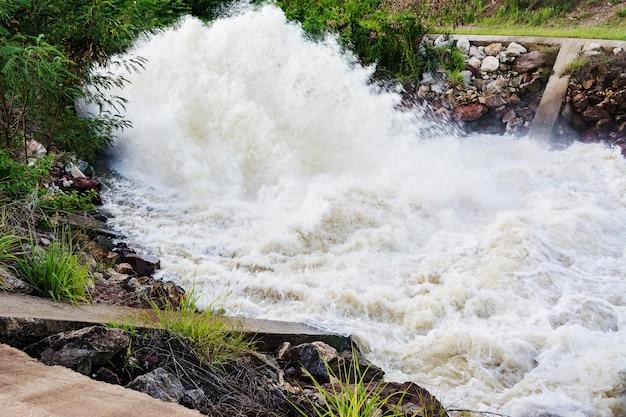 Bewegungsunschärfe des wasserfalls vom überlauf der verdammung auf regenzeit, nakhonsawan, thailand