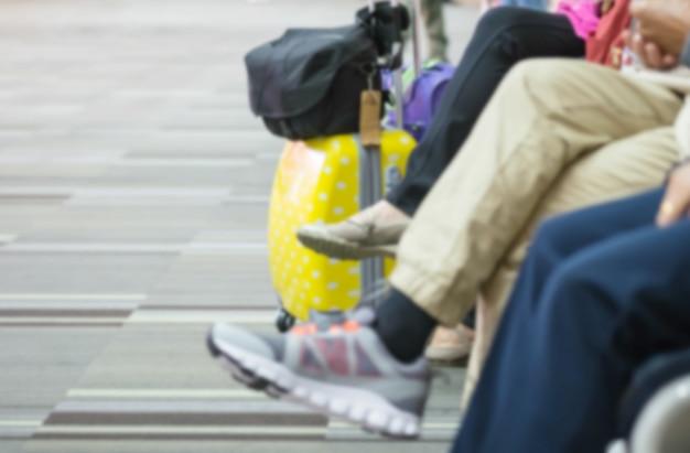 Bewegungsunschärfe von beinen von passagieren, die warten, um flüge einzusteigen