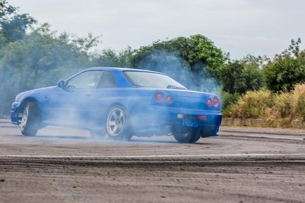 Bewegungsunschärfeautreiben, treibendes auto des berufsfahrers auf rennstrecke mit dem rauchen.