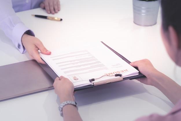 Bewerbungsgespräch im büro, bearbeitung wieder auf überprüfung. selbstbewusster umgang mit dem lebenslauf, personalvermittler erhält lebenslauf.