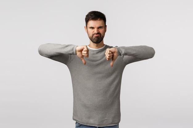 Bewertung, kundenmeinung und gefühlkonzept. verärgerter und enttäuschter mürrischer, gestörter erwachsener bärtiger mann im grauen pullover, der mit hasserfüllter miene ein gesicht verzieht, daumen runter zeigt, geste ablehnt