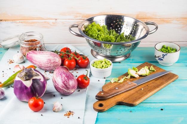 Bewirtschaften sie frischen gemüsebestandteil und küchengerät auf blauem holztisch