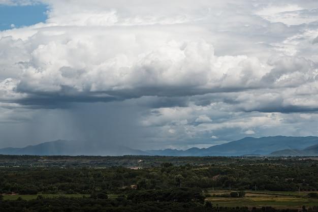 Bewölkter himmel in der regenzeit, regen über brennendem rauch der landwirtschaft, natur und umweltverschmutzungskonzept.