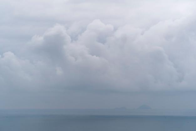 Bewölkter morgen über meerwasser. landschaftssonnenaufgang auf hon chong kap, nha trang, khanh hoa provinz, vietnam. reise- und naturkonzept. bedeckter morgen, wolken und meerwasser