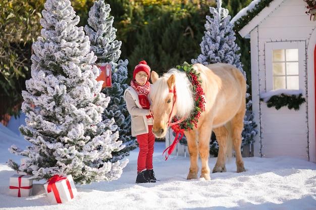 Bewundernswerter junge mit brille hält sein entzückendes pony mit festlichem kranz nahe dem kleinen holzhaus und den schneebedeckten bäumen.