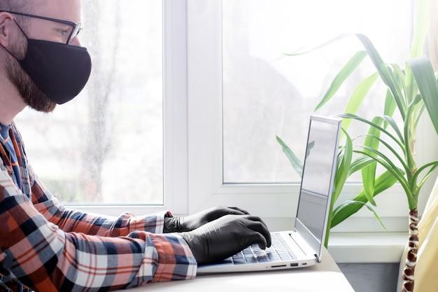 Bewusste selbstisolation. ein mann mit schutzmaske und handschuhen arbeitet an einem laptop. online-arbeit. eine viruspandemie in der welt.