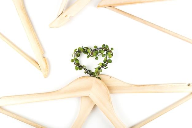 Bewusster konsum slow-fashion-konzept herz von kleiderbügeln mit grüner pflanze auf we...