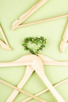 Bewusster konsum slow-fashion-konzept herz von kleiderbügeln mit pflanzen auf grünem hinter...