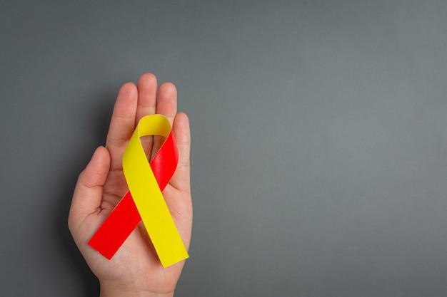 Bewusstsein zum welthepatitis-tag mit rot-gelbem band