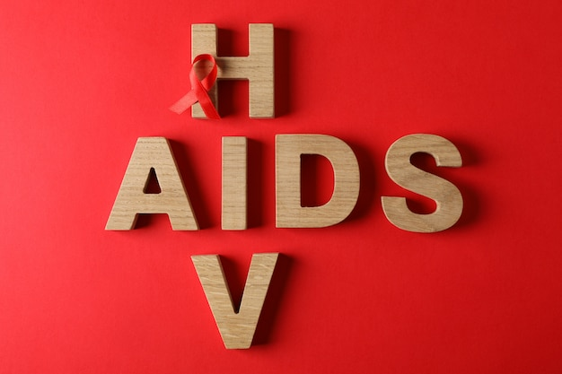 Bewusstseinsband und wörter aids und hiv auf roter wand, raum für text