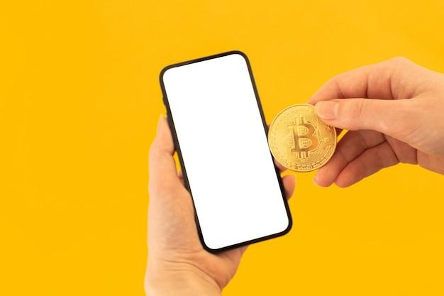 Bezahlen sie mit bitcoin-modell mit leerem weißem bildschirm, gelbem hintergrund mit handy und bitcoin-münze in der hand einer frau, kopieren sie platzfoto