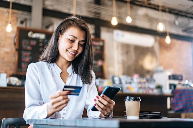 Bezahlen sie waren mit kreditkarte über ein smartphone in einem café.