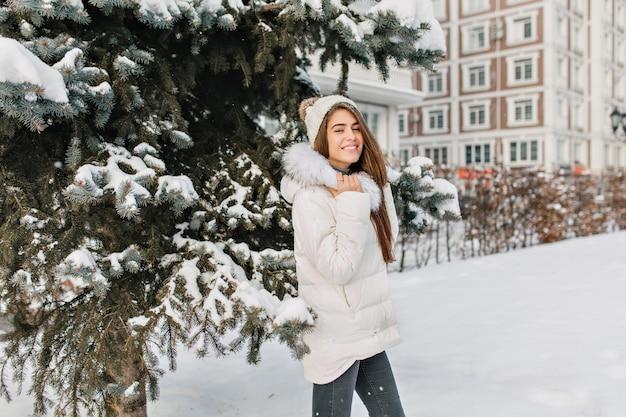 Bezaubernde blonde frau in der weißen jacke und in den schwarzen jeans, die während des spaziergangs im winterpark aufwerfen. foto im freien von hübscher modischer frau, die spaß im dezembermorgen hat.