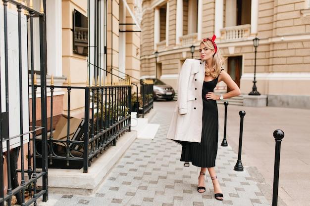 Bezaubernde blonde frau in stilvollem schwarzen kleid und schuhen mit hohen absätzen, die morgens im freien posieren. schönes blondes mädchen in eleganter kleidung, das zeit auf der straße verbringt und lächelt.