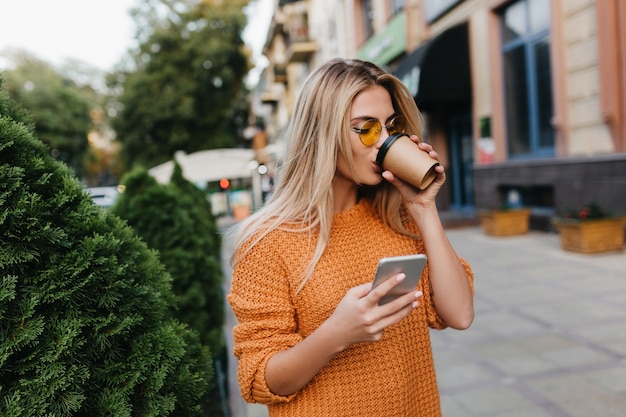 Bezaubernde blonde junge frau, die auf telefonische nachricht wartet, während sie kaffee auf der straße trinkt
