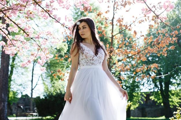 Bezaubernde brunettebraut geht in weißes kleid unter blühenden kirschblüte-bäumen