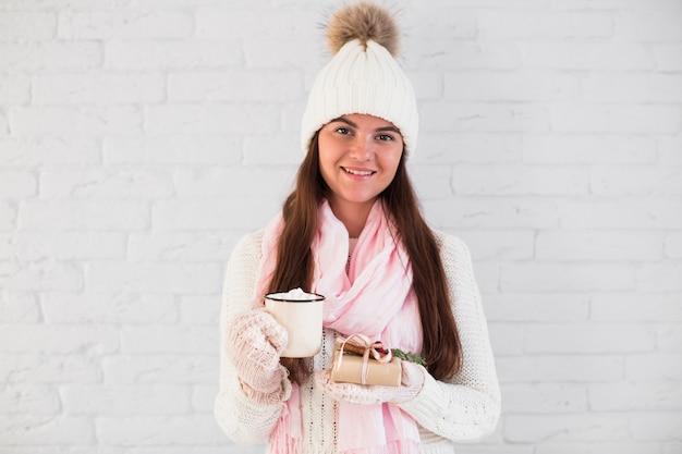 Bezaubernde dame in handschuhen, mütze und schal mit becher und geschenkbox