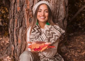 Bezaubernde Frau mit Herbstlaub nahe Baum