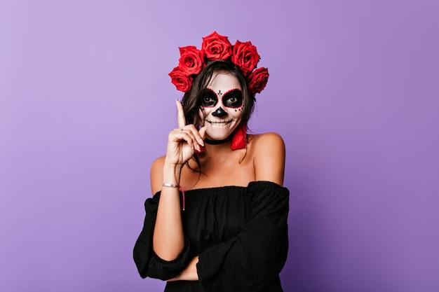 Bezaubernde frau mit rosen im schwarzen haar, die auf halloween-party warten. glückliches lateinisches weibliches modell mit lächelndem vampirgesichtsmalerei