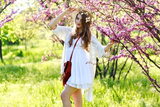 Bezaubernde hübsche junge frau mit langen haaren im sommerhut, weißes helles kleid, das im sonnigen garten auf blühendem sakura-hintergrund geht. entspannung, lächeln in die kamera, leichte kleidung, sensibilität, freude