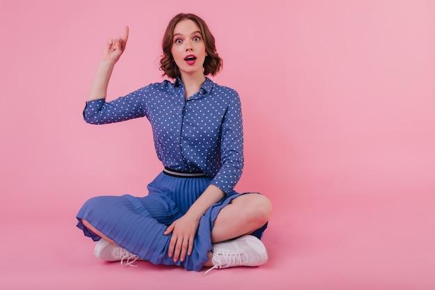 Bezaubernde junge dame in blauer kleidung, die mit überraschtem gesichtsausdruck auf dem boden sitzt. innenporträt des brünetten charmanten mädchens im rock.