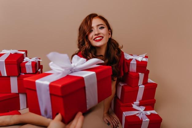 Bezaubernde langhaarige frau, die neben weihnachtsgeschenken aufwirft. romantisches ingwermädchen, das neujahrsparty genießt.