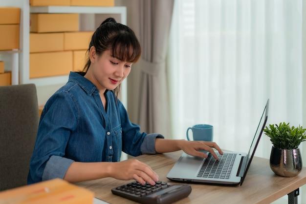 Bezaubernde schöne asiatische jugendlichinhaber-geschäftsfrau arbeiten zu hause für das on-line-einkaufen, berechnen preis von waren mit laptop mit büroausstattung, unternehmerlebensstilkonzept