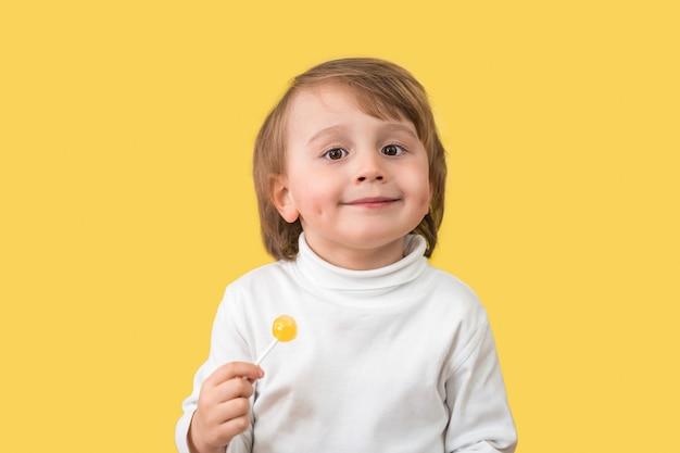 Bezaubernder entzückender kleiner junge, der mit grübchen lächelt, die vorne schauen und lutscher halten