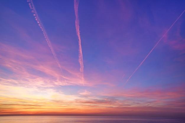 Bezaubernder magischer gradientenhimmel mit flugzeugspuren nach sonnenuntergang