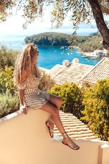 Bezaubernder weiblicher reisender, der auf wand sitzt und meer betrachtet